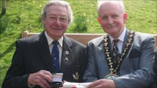 Les Jones (left) receiving his award from Powys council chair Garry Banks
