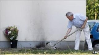 A man covers the traces of marks left by a French Telecom employee who set himself alight in a company carpark