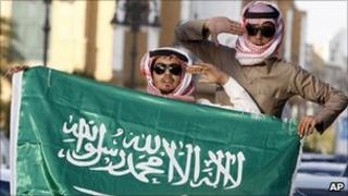 Saudi Arabian men carry a national flag during celebrations in support for the King, Riyadh, 18 March, 2011.