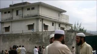 Local residents and media persons are seen outside the house of where al-Qaida leader Osama bin Laden was caught and killed in Abbottabad, Pakistan Thursday, May 5, 2011.