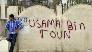 "A Pakistani man leans against a wall bearing the graffiti ""Osama Bin Town"" near the hideout house of slain Al-Qaeda leader Osama bin Laden"