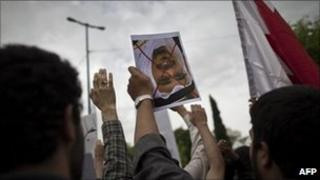 """An Iranian student holds upside down a portrait of Bahrain's King Hamad bin Issa al-Khalifa with a red """"X"""" drawn across it during a protest outside the Bahrain embassy in Tehran on 30 April 2011"""
