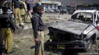 Policemen and paramilitary forces stand at the scene of a suicide bomb blast in Dir, northwest Pakistan April 4, 2011
