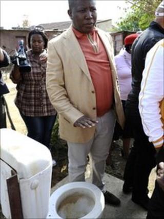 Julius Malema is shown an open-air toilet in Rammulotsi township, near Viljoenskroon