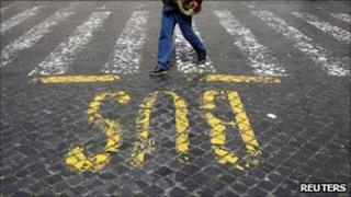 A man walks past a bus sign painted on a street in Rome (archive image)