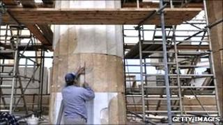 Man doing restoration work on a column of the acropolis