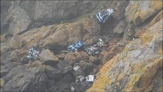 Vehicles at the bottom of the cliffs at Pleinmont