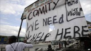 Haiti earthquake survivor with banner appealing for help