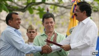 President Lobo (l) and former president Zelaya (r) shake hands as Colombian President Juan Manuel Santos (m) applauds