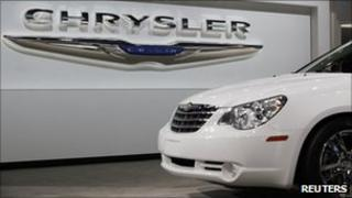 A Chrysler Sebring sits in front of the Chrysler logo