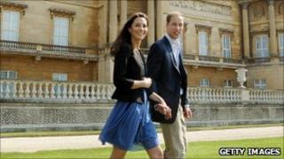 The Duke and Duchesss of Cambridge hold hands, the Duchess wearing a blue dress.
