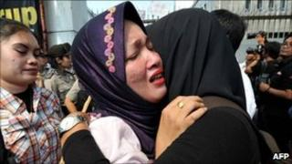 Een Nuraeni (L) daughter of Indonesian migrant worker Ruyati, cries during a protest against the execution of her mother outside the Saudi Arabian embassy in Jakarta on June 21, 2011