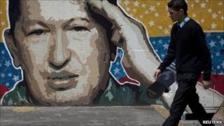A man walks past graffiti depicting Venezuelan President Hugo Chavez in Caracas 27 June, 2011.