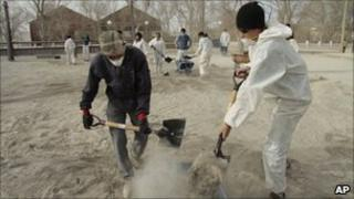 Volunteers remove volcanic ash, brought by Chile's Puyehue-Cordon Caulle volcano, from the ground in Ingeniero Jacobacci in southern Argentina, on 20 June, 2011