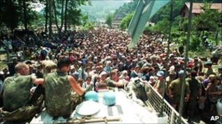 File picture dated 13 July 1995 showing Dutch UN peacekeepers sitting on top of an APC while Muslim refugees from Srebrenica, eastern Bosnia, gather in the village of Potocari, some 5km north of Srebrenica