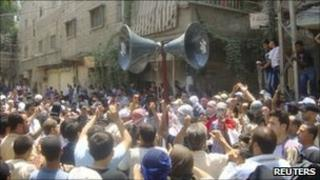 Anti-government demonstrators march through the streets after Friday prayers in Hajar al-Asswad in Damascus - 8 July 2011