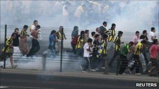 Fenerbahce supporters in clouds of tear gas on the main road to Bosphorus Bridge linking Asia to Europe during a protest in Istanbul, Turkey on 10 July