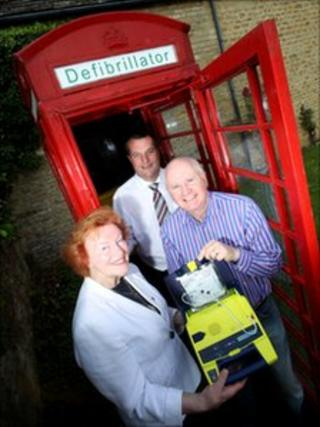 Red phone box and people with heart defibrillator