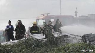 Firefighters in Recife, Brazil, spray flame retardant on the crashed L410
