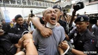 Police detain a supporter of the Bersih electoral reform coalition during a rally in Kuala Lumpur July 9, 2011