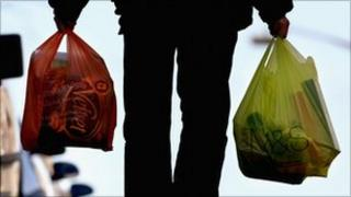 A shopper carrying two carrier bags of shopping