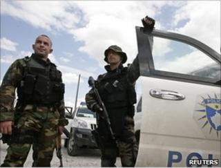 Kosovan policemen stand beside a vehicle in Mitrovica, 26 July