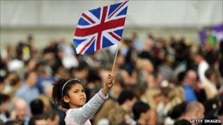 Girl in the crowd at Trafalgar Square waves a Union Flag