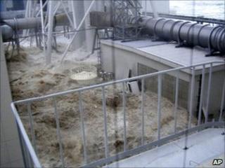 Tsunami waves gush into a complex near the Unit 4 reactor at the Fukushima Dai-ichi nuclear complex in Okuma