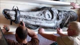 Museum staff unload the fossil