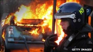 Police officer stands in front of a car on fire in Hackney