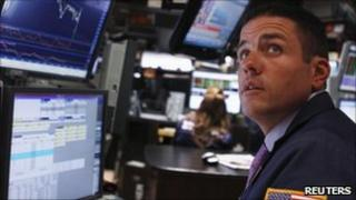 A trader works on the floor of the New York Stock Exchange as he listens to an announcement by the Fed in New York August