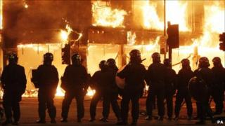 Riot police infront of burning building in Tottenham, 2011