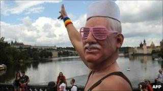 A man wearing a mask of Czech President Vaclav Klaus gestures as he takes part in the first gay pride festival in the Czech capital Prague, 13 August 2011