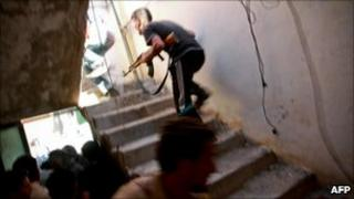 A rebel fighter runs up stairs during fighting in Zawiya, 13 August