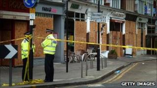 Police stand guard in front of boarded up shops and businesses in Ealing