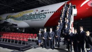 Members of the newly named 30-man squad for next month's rugby World Cup stand on the stairs of a Qantas jet in Sydney