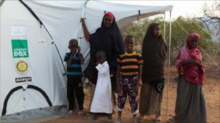 Families outside their new tent at Ifo II camp on Thursday 18 August 2011 - (Photo: BBC's Kelvin Brown)
