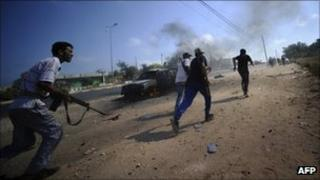 Libyan rebels run for cover during fighting against regime forces near Jaddayim west of Tripoli, on August 21, 2011