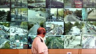 Police officer standing in front of CCTV screens