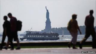 People walk along the waterfront in view of Liberty Island, New York