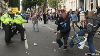 A man avoids being tripped by a member of the public as he runs down the road at the Notting Hill Carnival on August 29 after a person was stabbed