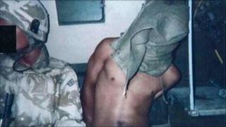 A hooded Iraqi detainee