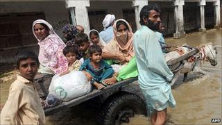 A Pakistani family ride on a donkey-cart through flood waters