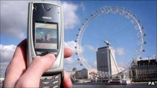 A mobile phone is used to take a picture of the London Eye