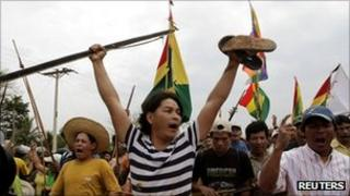 Indigenous protesters brandish bows and wave flags as they continue their march