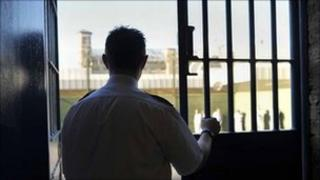 Prison officer stands against iron bars