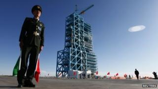 Chinese soldier stands beside Long March II-F rocket loaded with China's unmanned space module Tiangong-1 at the launch pad in the Jiuquan Satellite Launch Center, Gansu province on Wednesday