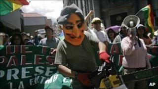 A demonstrator wearing an Evo Morales mask and holding a chainsaw marches in La Paz, Bolivia
