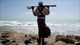 Armed man on coast of Somalia with MV Filitsa, seized by pirates, in distance - 26 January 2010