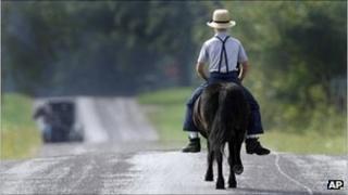 An Amish boy riding a horse
